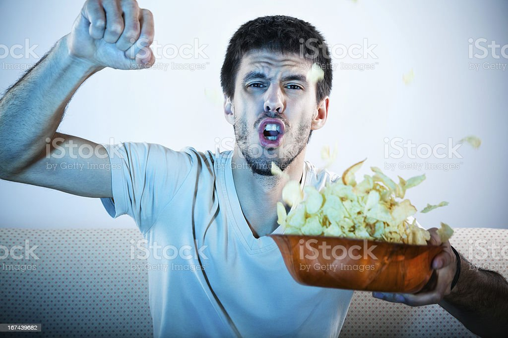 Man watching television with a bowl of chips stock photo