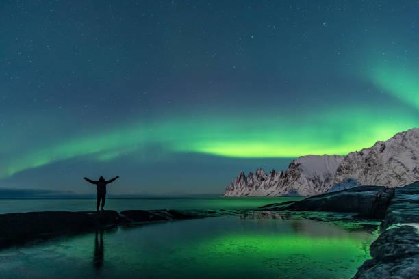 Man watching the northern lights, Aurora Borealis, Devil Teeth mountains in the background, Tungeneset, Senja, Norway stock photo