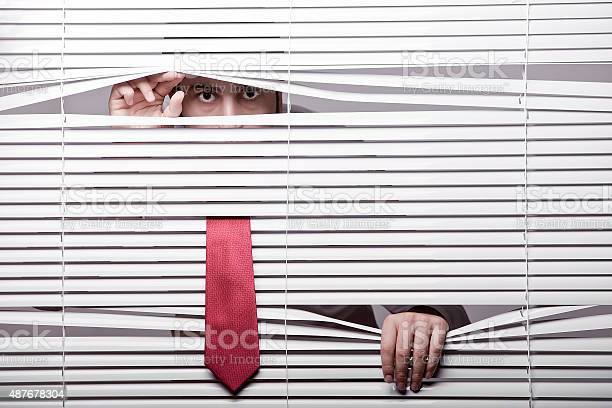 Man Watching Through Window Blinds Stock Photo - Download Image Now