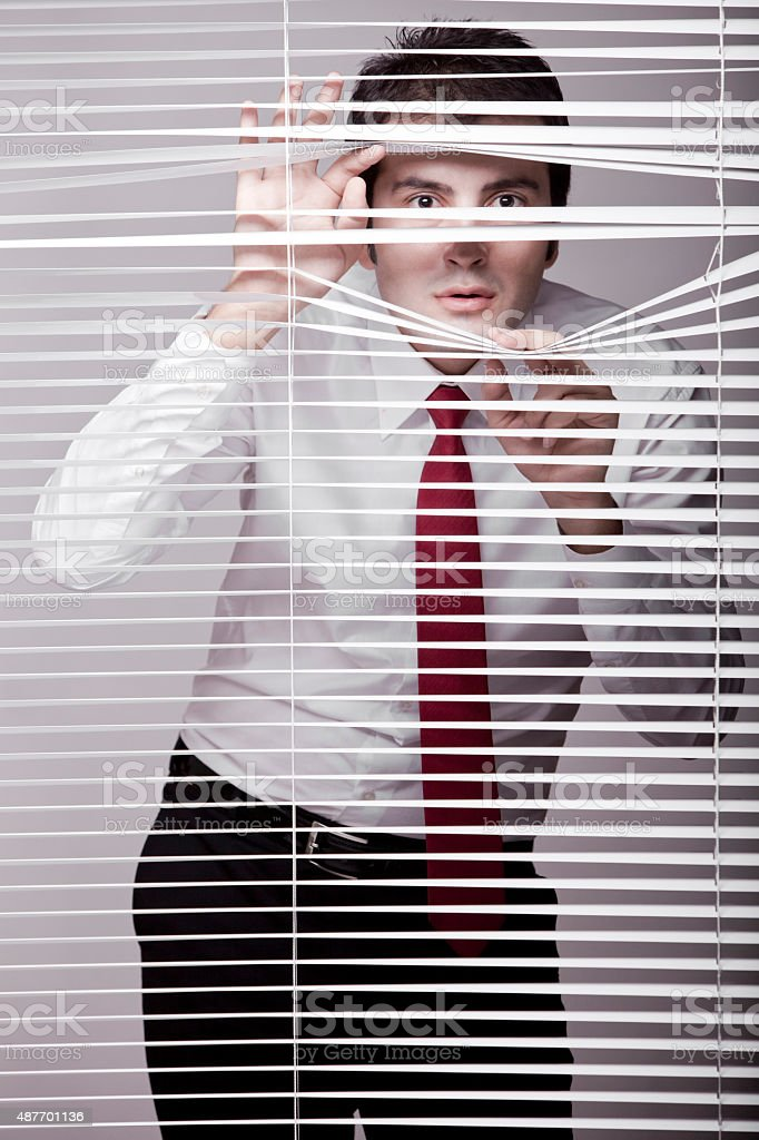 Man Watching through window blinds stock photo