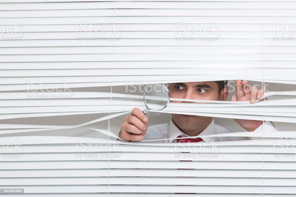 Man Watching through window blinds royalty-free stock photo