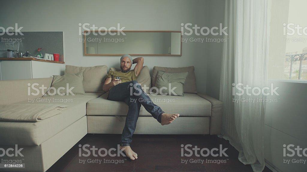 Man watching TV at home stock photo