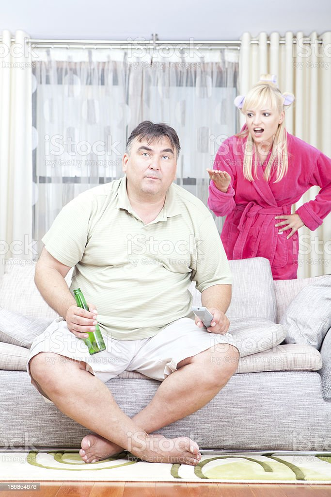 Man watching TV home with wife screaming at him royalty-free stock photo
