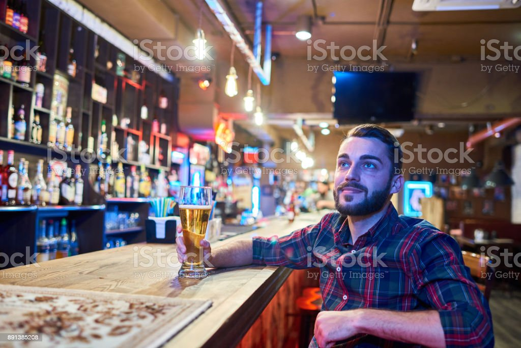Man Watching TV in Beer Pub stock photo