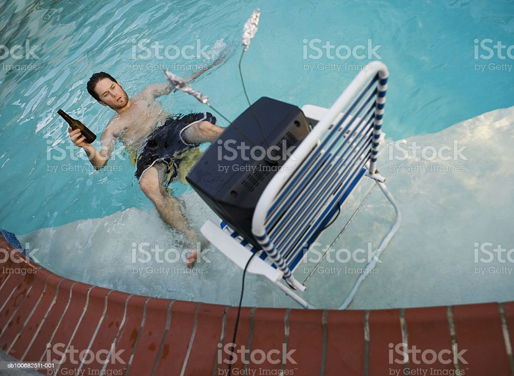 Man watching tv in swimming pool, drinking beer 免版稅 stock photo