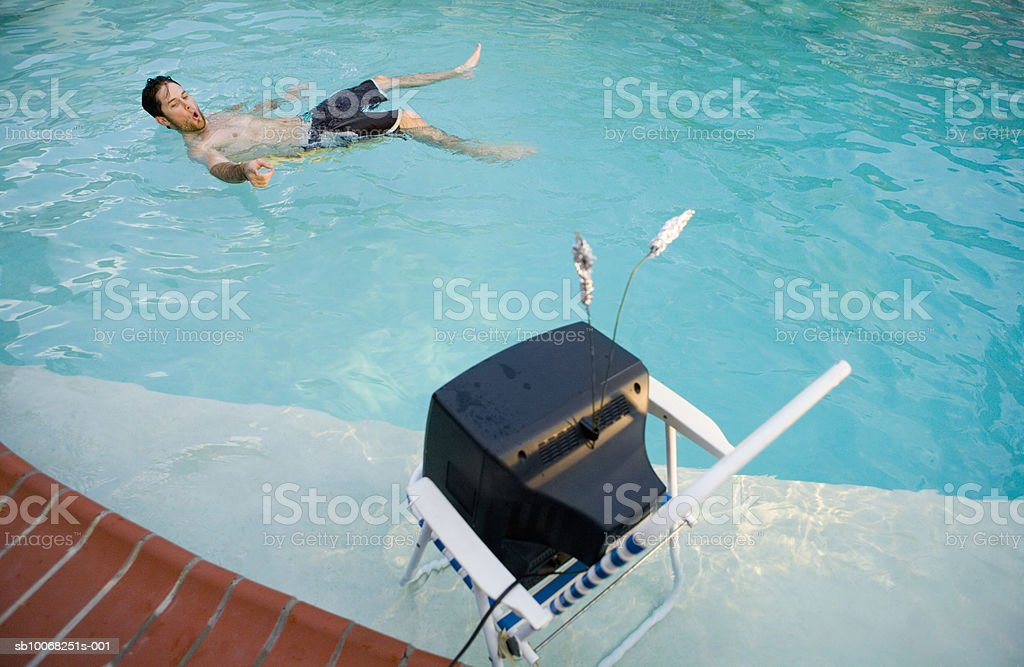 Man watching tv in swimming pool royalty-free stock photo