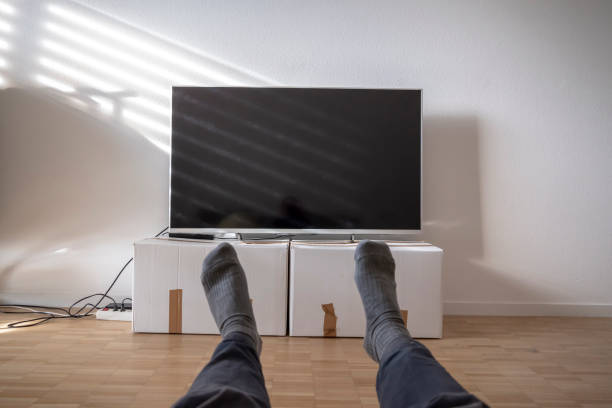 Man Watching TV on Cardboard Box stock photo