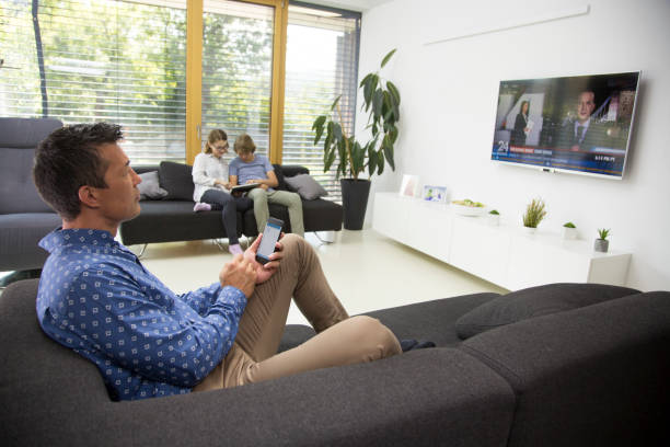 man watching tv - family watching tv stock photos and pictures