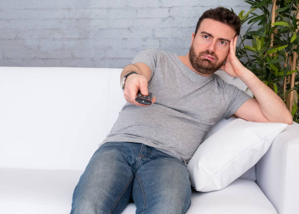 man op de bank thuis zitten tv kijken - lazy stockfoto's en -beelden