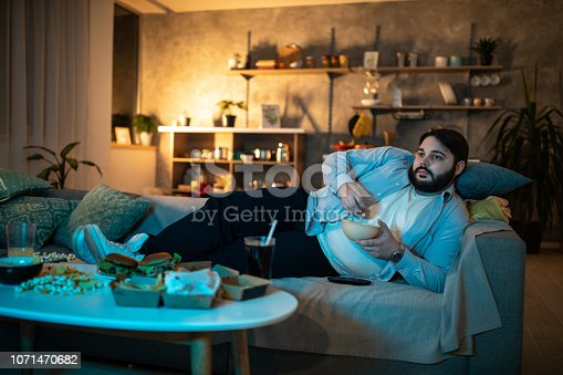 Lazy man lying on side on sofa and watching TV while eating popcorn
