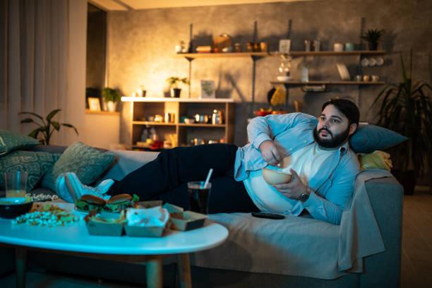 看電視節目的人 - 不健康飲食 個照片及圖片檔