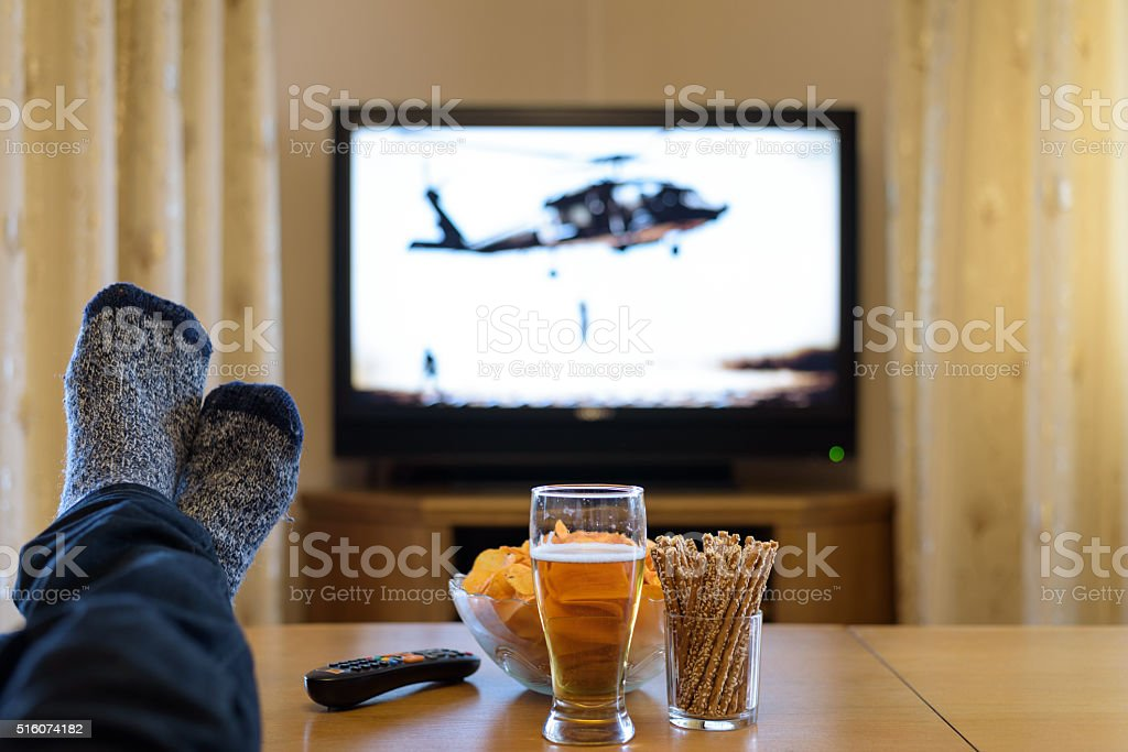 man watching TV (television) war movie with feet on table stock photo