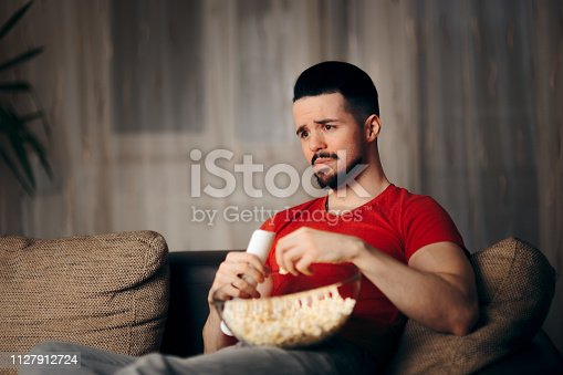 istock Man Watching TV While Snacking on Pop Corn 1127912724