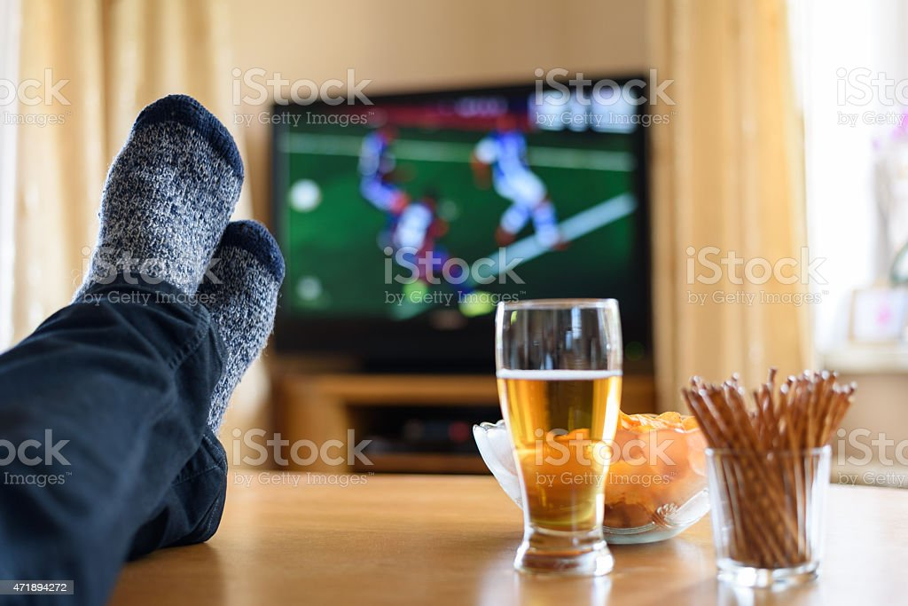 Man watching tv with feet up on table with beer and snacks stock photo