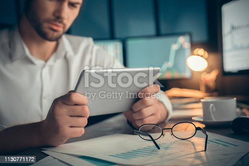 istock Man watching video or read the book at screen tablet 1130771172