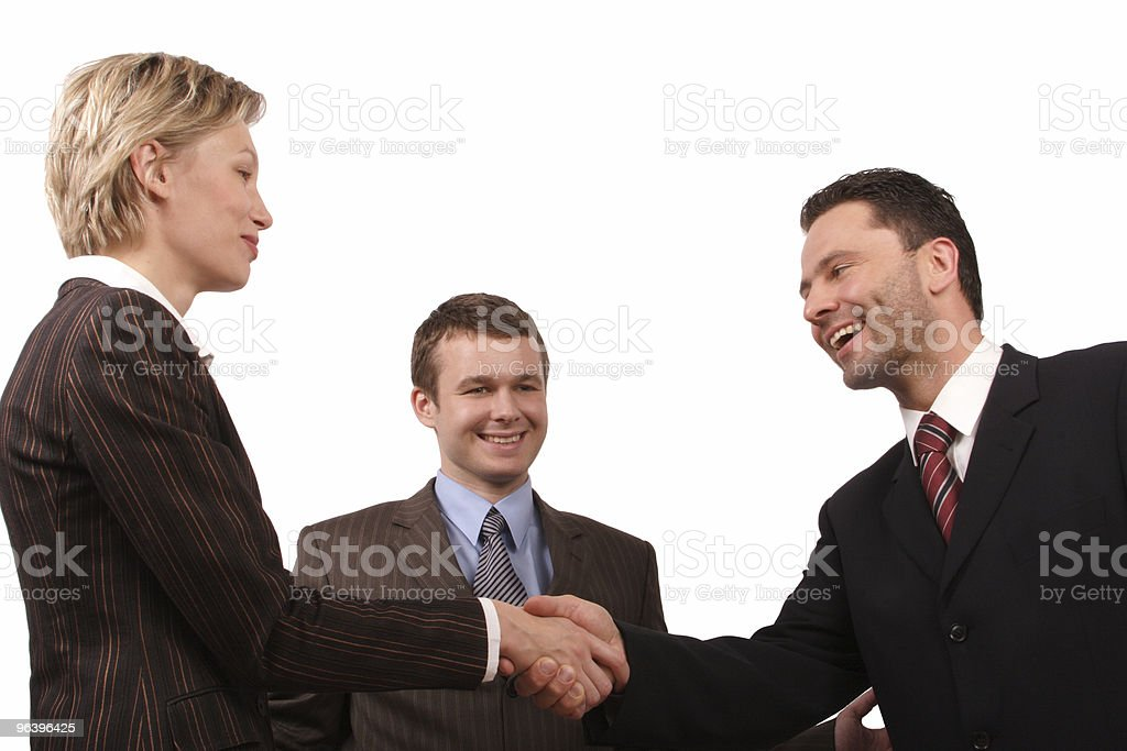 Man watching woman and another man shake hands, all smiling - Royalty-free Agreement Stock Photo