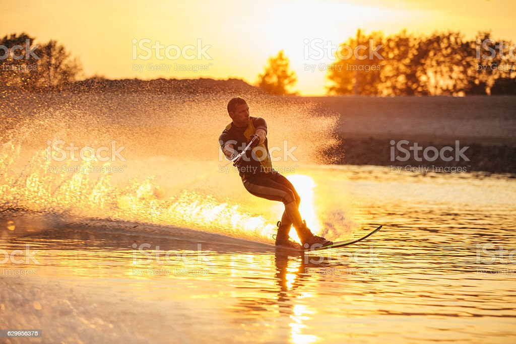 Man water skiing at sunset stock photo