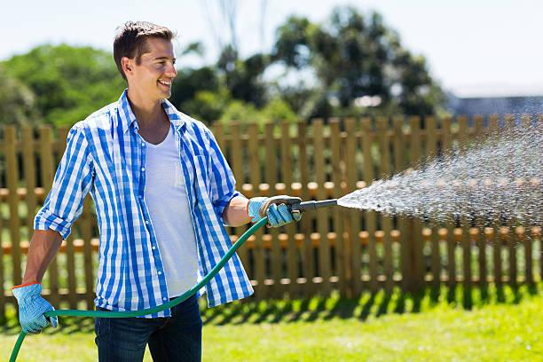 man watering garden - garden hose stock pictures, royalty-free photos & images