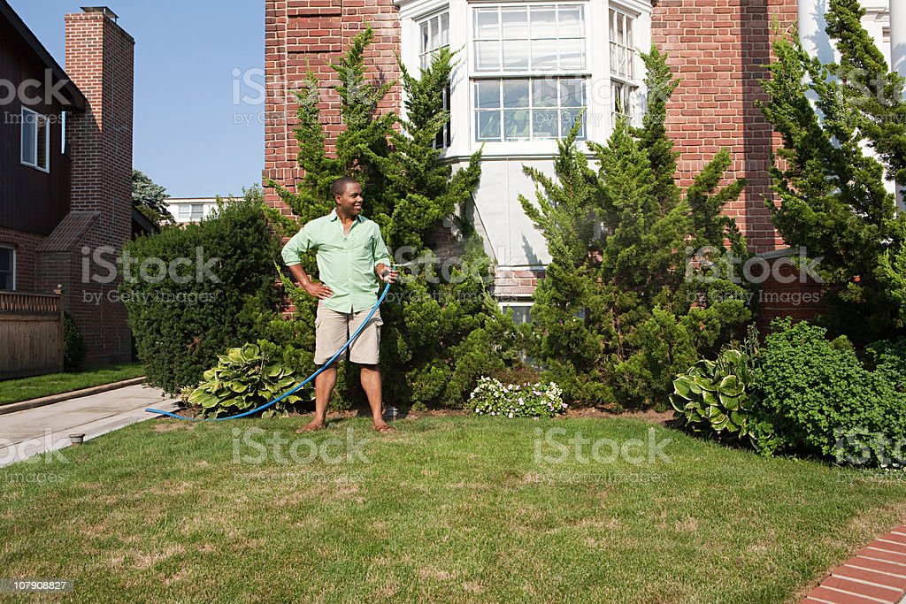 Man watering grass with hosepipe stock photo