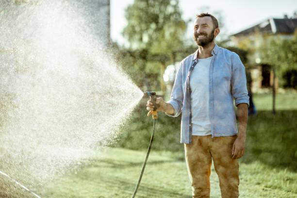 Man drenken groene gazon op de achtertuin foto