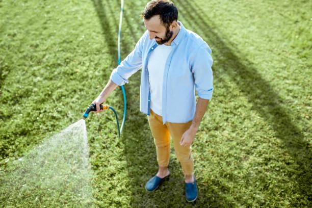 Mann wässert grünen Rasen – Foto