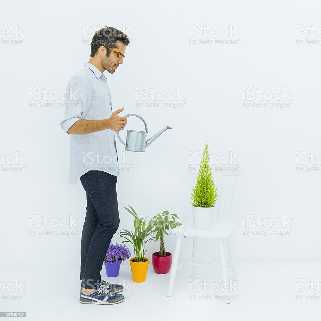 Man Watering His Plants In A White Home Stock Photo Download