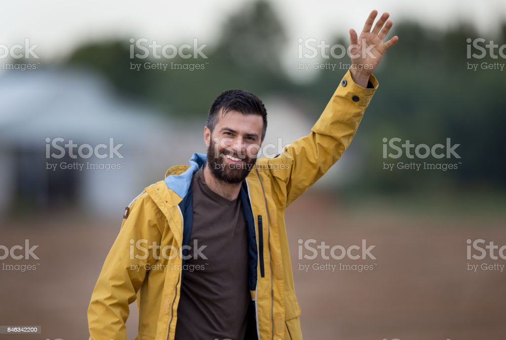 Man waving hand in field stock photo