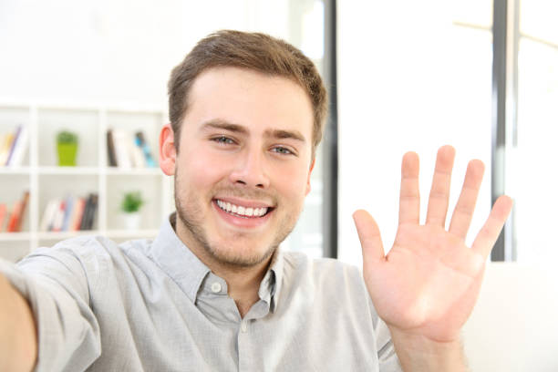 man waving on a video call at home - webcam stock photos and pictures