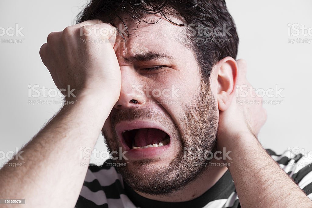 A man wearing a black and white shirt cries out in pain stock photo