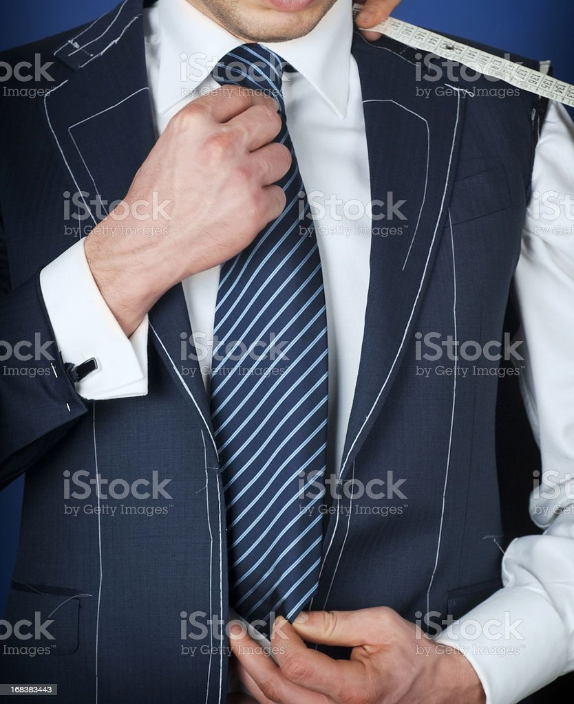 Man wearing a black coat, white suit and striped blue tie.  stock photo