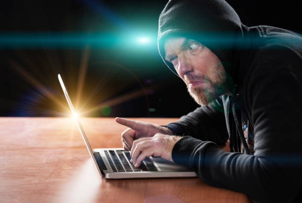 Man wearing a black hood uses a laptop Man wearing a black hood uses a laptop creepy stalker stock pictures, royalty-free photos & images