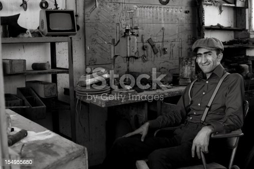 istock Man wearing a cap in an old fashioned workshop 154955680