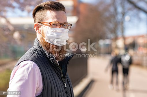 A man is wearing a face mask to protect himself from virus and particles. There are cherry blossom trees behind him.
