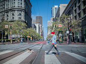 A man wearing a face mask walking across the street with his dog in San Francisco during shelter in place. March 25th, 2020.