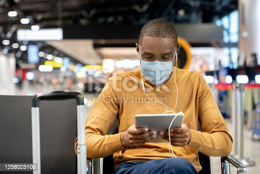 istock Man wearing a facemask at the airport while watching movies on his tablet at the gate 1258025105