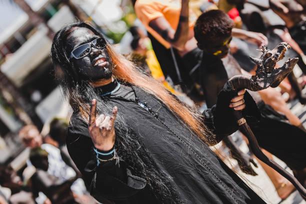 mann trägt einen langen schwarzen mantel und sonnenbrille machen die zeichen der hörner - rock n roll kleider stock-fotos und bilder