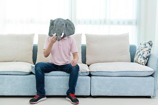 Man wearing a mask sitting on sofa
