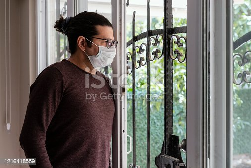 Man wearing a medical mask staying at home under quarantine during Coronavirus outbreak