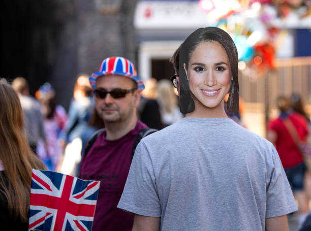 man wearing a megan markle face mask while celebrating the marriage of meghan markle and prince harry at st george's chapel at windsor castle - meghan markle стоковые фото и изображения