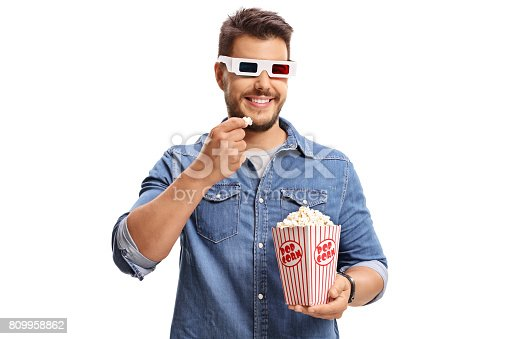 istock Man wearing a pair of 3D glasses and eating popcorn 809958862