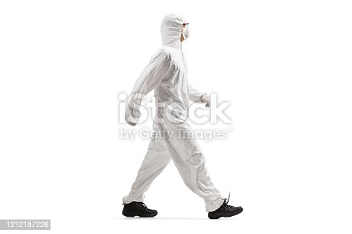 Full length profile shot of a man wearing a protective suit and mask and walking isolated on white background