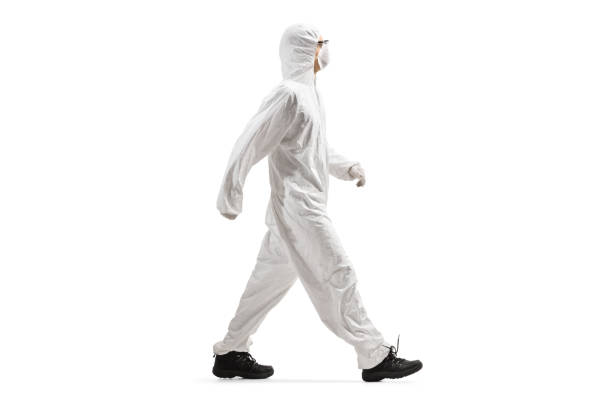 man wearing a protective suit and mask and walking - tuta protettiva foto e immagini stock