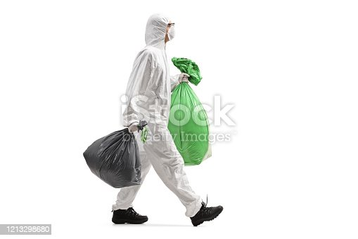 Full length profile shot of a man wearing a protective suit and walking with waste bags isolated on white background