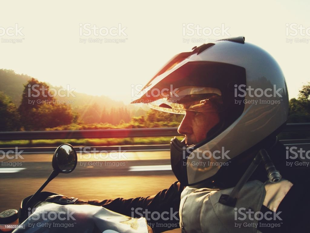Man wearing a silver helmet riding a motorcycle at sunset stock photo