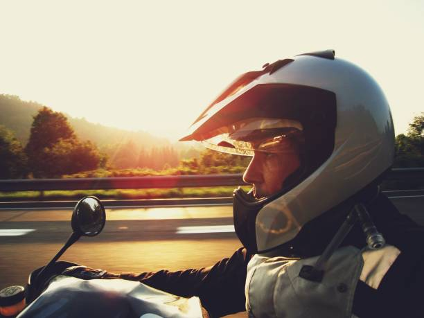 man wearing a silver helmet riding a motorcycle at sunset - crash helmet stock photos and pictures