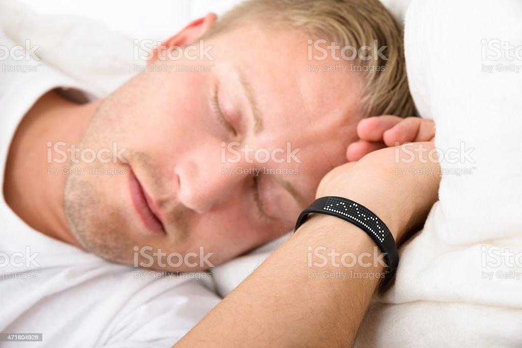 Man wearing a smart fitness tracker on wrist while sleeping stock photo
