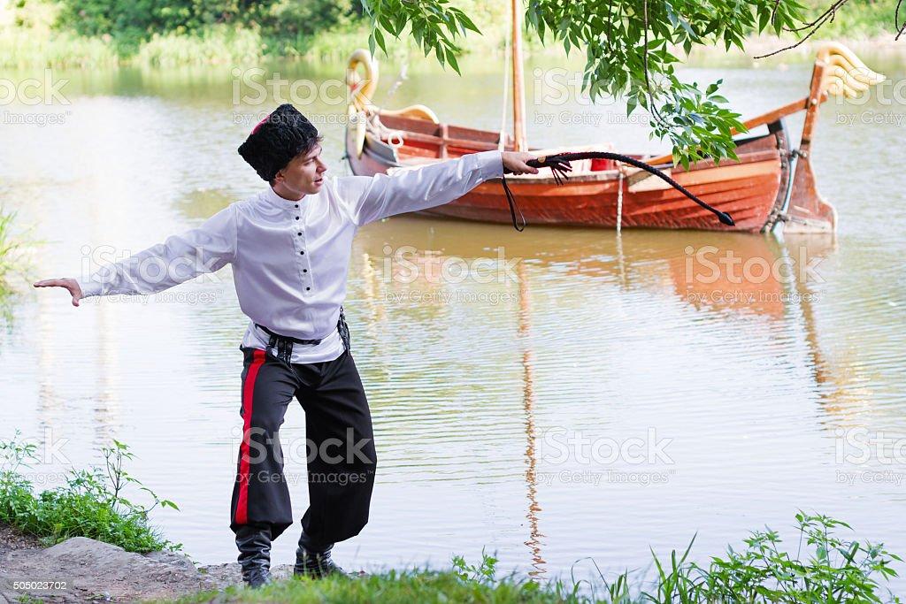 man wearing a stylized Ukrainian costumes posing with whip stock photo