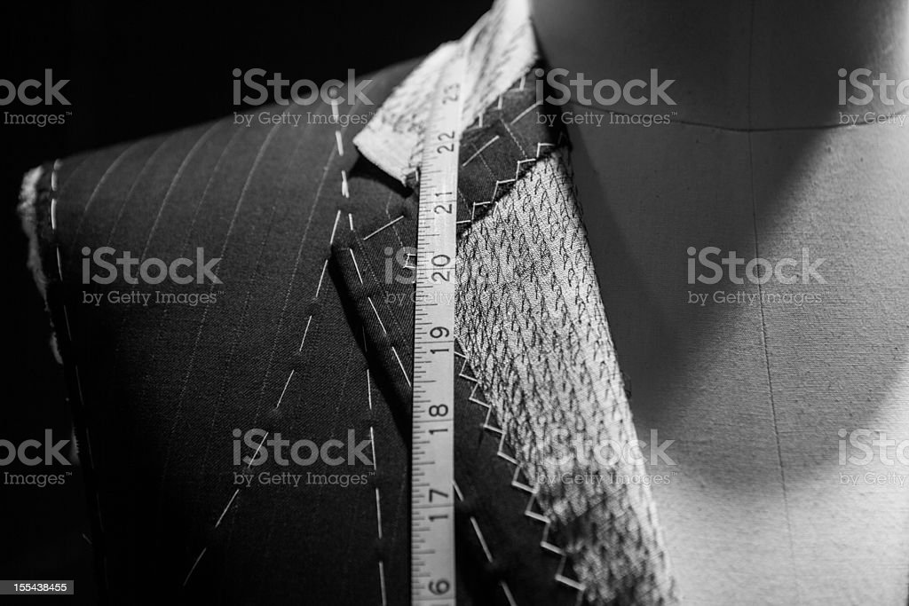 Man wearing a suit close-up with tape measure around neck stock photo
