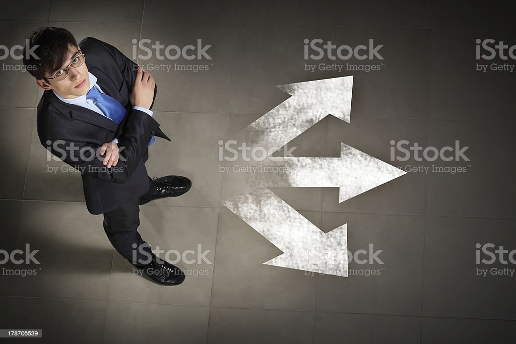 Man wearing a suit with arms folded and white arrows stock photo
