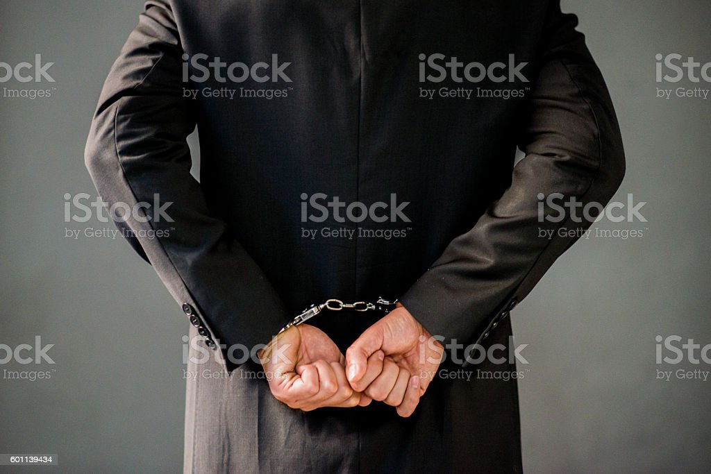 man wearing a suit with his wrists handcuffed behind stock photo